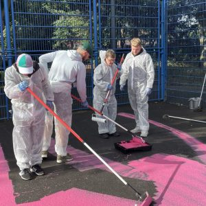 Chris and Jordan from 'Options for Life', together with support workers Nathan and Josh, helping to paint the basketball court